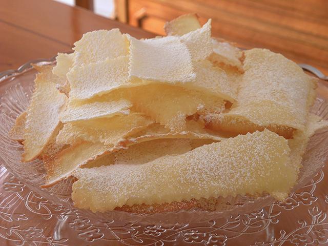 Frappe di Carnevale Senza Glutine e Lattosio-Cospargere le Frappe con Zucchero a Velo Senza Glutine